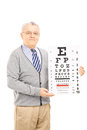 Senior man holding eyesight test isolated on white background Stock Photos