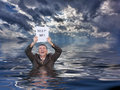 Senior man holding help me paperwork in water conceptual image of businessman suit up to waist deep worried about drowning and Stock Image