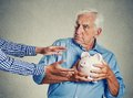 Senior man holding piggy bank suspicious protecting savings closeup portrait grandfather looking trying to protect his from being Stock Photos