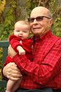 Senior man holds grandbaby in red as they smile Royalty Free Stock Images