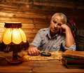 Senior man in homely interior with magnifier fell asleep wooden Royalty Free Stock Images