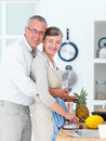 Senior man  hugging woman in kitchen Stock Image