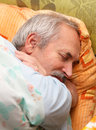 Senior man laying in his bed taking a nap Stock Images