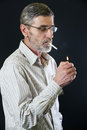 Senior man lighting cigarette middle aged a studio shoot on the black background Royalty Free Stock Photography