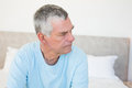 Senior man looking away on bed thoughtful while sitting at home Stock Photos