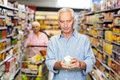 Senior man looking at canned food Royalty Free Stock Photo