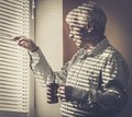 Senior man looking through jalousie with cup out the window Royalty Free Stock Image