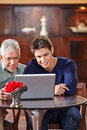 Senior and man looking at laptop computer young men in a café Royalty Free Stock Photo