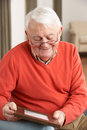 Senior Man Looking At Photograph In Frame Royalty Free Stock Photo