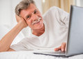 Senior man is lying in bed with laptop and looking at the camera Royalty Free Stock Photo