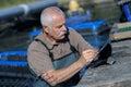 Senior man managing fish farm Royalty Free Stock Photo