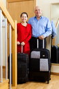 Senior man and mature girl with suitcases men near door at home Stock Photo