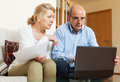 Senior man with mature wife reading business documents men and using laptop in home interior Royalty Free Stock Images