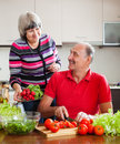 Senior man and mature woman cooking vegetables men women lunch in home kitchen Stock Images