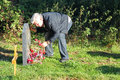 Senior man mourning in a cemetery placing flowers by the headstone of grave and someone who has died Royalty Free Stock Photo