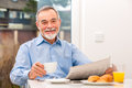 Senior man with a newspaper happy at breakfast Stock Photography