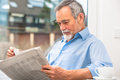Senior man with newspaper happy at breakfast Royalty Free Stock Photo