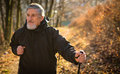 Senior man nordic walking enjoying the outdoors the fresh air getting the necessary exercise Royalty Free Stock Photos