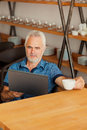 Senior man with notebook sitting at the kitchen an and drink coffee Royalty Free Stock Image