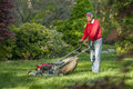 Senior man owing grass mowing the in his yard Stock Images
