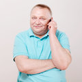 Senior man with phone over white cheerful middle aged talking on mobile background Stock Photo