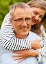 Senior man piggybacking his wife at the garden Stock Images