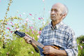 Senior man playing mandolin outside on the green background Stock Photo