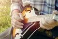 Senior man playing mandolin outside on the green background Stock Image