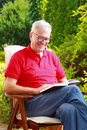 Senior man portrait image of sitting in garden at home and reading book Stock Photography