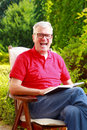 Senior man portrait image of sitting at nursing home garden and reading book while looking at camera and laughing Stock Photography