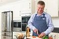 Senior Man Preparing Meal In Kitchen Royalty Free Stock Photo