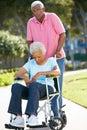 Senior Man Pushing Unhappy Wife In Wheelchair Stock Image