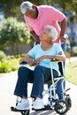 Senior Man Pushing Wife In Wheelchair Stock Images