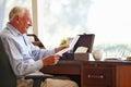 Senior man putting letter into keepsake box sitting down reminiscing Royalty Free Stock Image