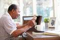 Senior man putting letter into keepsake box sitting down smiling Royalty Free Stock Images