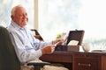 Senior man putting letter into keepsake box smiling at camera Royalty Free Stock Photo