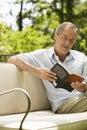 Senior Man Reading Book In Backyard Royalty Free Stock Photo