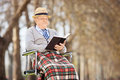 Senior man reading a book in park outside Royalty Free Stock Images