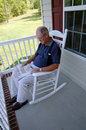 Senior man reading newspaper on front porch Royalty Free Stock Image