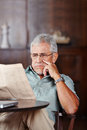 Senior man reading newspaper in retirement home a at table Stock Photo