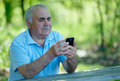 Senior man reading a text message on his phone mobile as he sits at rustic wooden table outdoors relaxing in the shade Royalty Free Stock Image