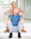Senior man receiving shoulder massage from wife Royalty Free Stock Images