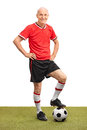 Senior man in a red jersey stepping over a football full length portrait of on field and looking at the camera isolated on Royalty Free Stock Photos