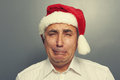Senior man in red santa hat unhappy Royalty Free Stock Image