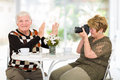 Senior man refusing to be photographed men by his wife at home Stock Photos