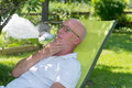 Senior man relaxing in the deckchair in his garden Royalty Free Stock Photo