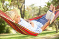 Senior Man Relaxing In Hammock With Book Stock Photos