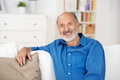Senior man relaxing at home smiling friendly sitting on a sofa in his living room looking the camera Royalty Free Stock Photos
