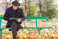 Senior man relaxing with a tablet computer one legged disabled sitting enjoying the fresh air and sunshine in an autumn park Royalty Free Stock Image