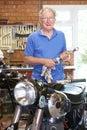 Senior Man Restoring Vintage Motorcycle In Garage Royalty Free Stock Photo